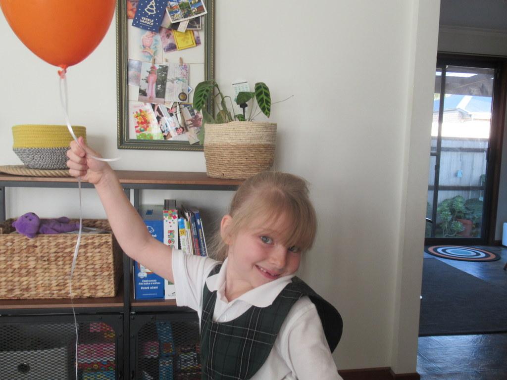 Stela s balonkem na oslavu toho, že se po karanténě mohla vrátit do školy.