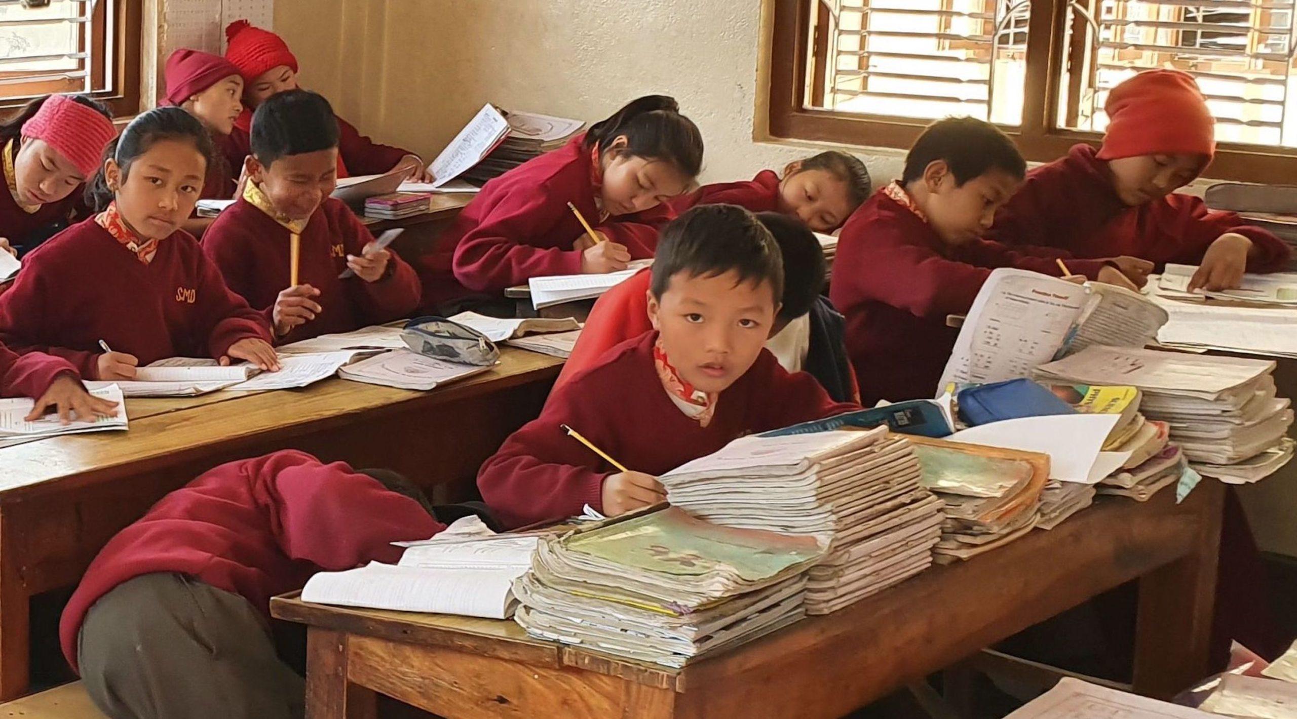 Škola má jen základní vybavení, ale třídy rozjasňuje červeň školních mundúrů a mnišských rouch, na stěnách visí motivační slogany a knihovna je dobře vybavená dětskými knihami v angličtině.